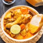 Poulet au curry dans un bol avec un morceau de baguette et un demi citron vert