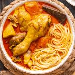 Poulet au curry avec nouilles dans un bol au-dessus d'une baguette découpée et en dessous d'une assiette de nouilles