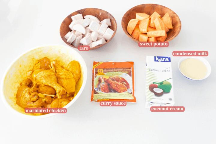 Poulet mariné dans un bol, morceaux de taro et patate douce dans des bols, sauce curry dans un sac, crème de coco dans un carton et lait concentré dans un bol