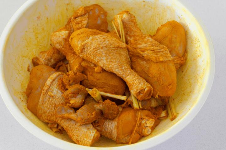 Pilons de poulet marinés à la poudre de curcuma dans un bol à la citronnelle