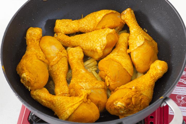 Pilons de poulet au curcuma dans un wok