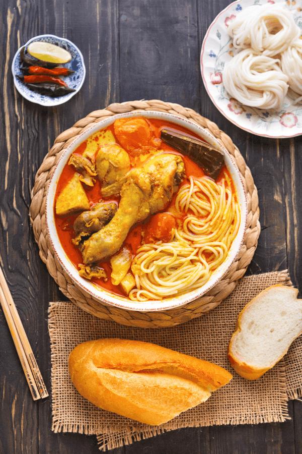 Poulet au curry vietnamien et nouilles dans un arc avec une assiette de nouilles de riz, des baguettes et une baguette