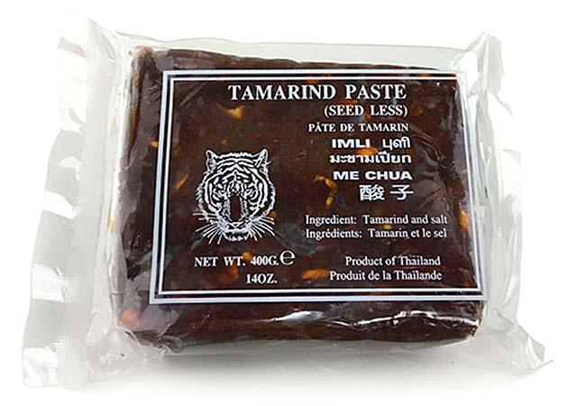 Le pad thaï au tamarin est fait avec du jus de tamarin extrait de pulpes de tamarin. Ceci est une image de bloc de tamarin dans un emballage en plastique transparent.