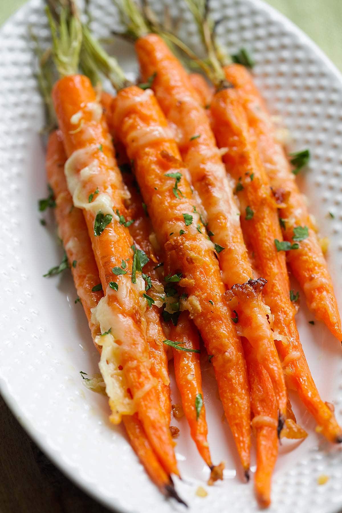 Une des meilleures recettes de carottes rôties à base de carottes, d'ail, de beurre et de parmesan sur une assiette.