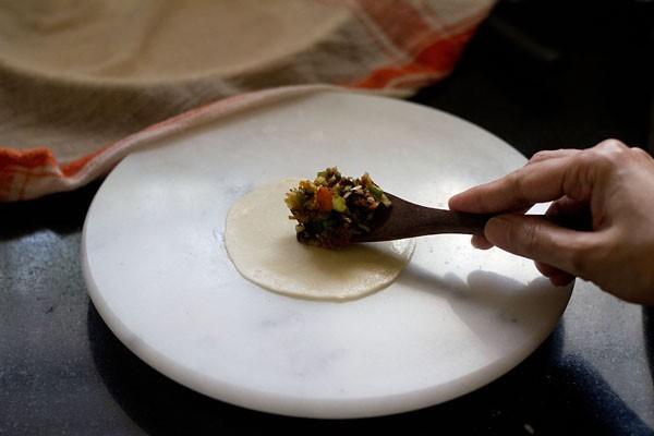placer la farce de légumes avec une cuillère en bois au centre de la pâte roulée