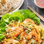 Salade de mangue vietnamienne sur une assiette avec une assiette de craquelins au sésame et un plat de sauce de poisson