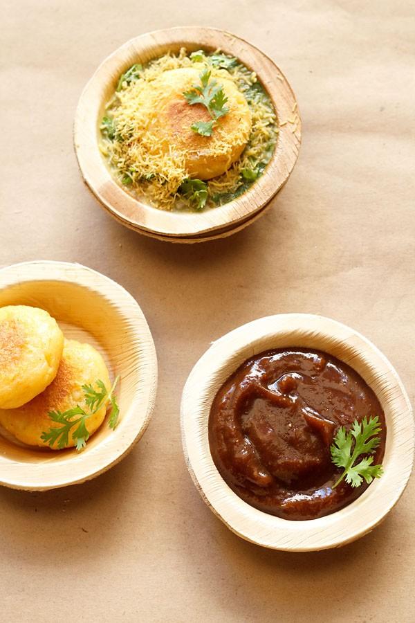 chutney de tamarin sucré garni d'un brin de coriandre et servi dans un bol de feuilles d'Arec sur un papier brun clair avec galettes de pommes de terre dans des bols de feuilles d'arec sur le côté gauche et galettes de ragda chaat sur le dessus