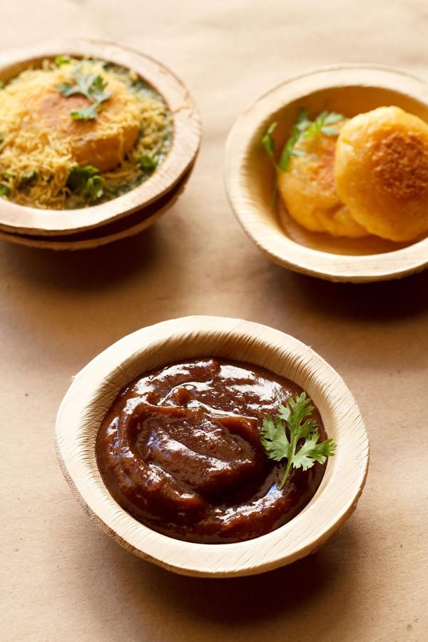 chutney de dattes au tamarin garni d'un brin de coriandre et servi dans un bol de feuilles d'Arec sur un papier brun clair avec galettes de pommes de terre et galettes de ragda chaat dans des bols de feuilles d'Arec placés sur le dessus