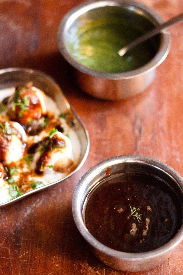 chutney de tamarin garni d'un brin de coriandre servi dans un bol en acier avec une assiette carrée de Dahi Vada conservée au centre gauche et chutney vert conservé dans un bol en acier sur le dessus