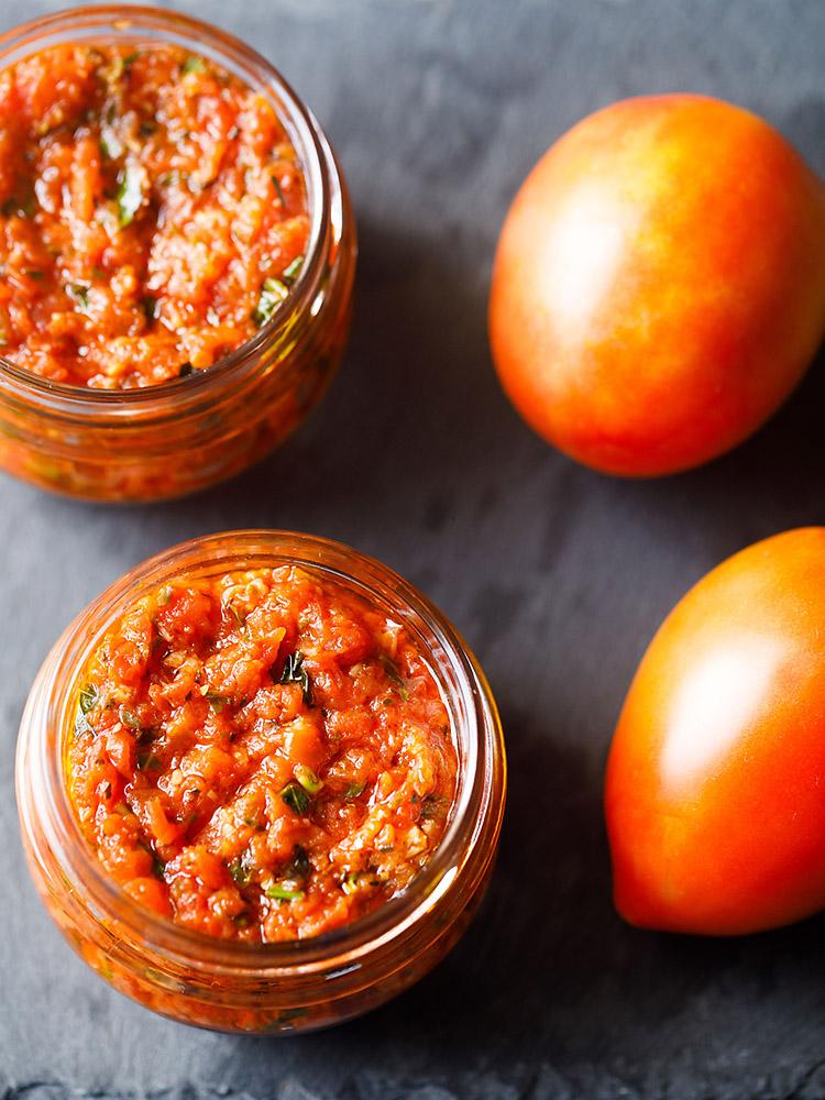 sauce à pizza dans deux petits bocaux en verre placés sur une ardoise gris foncé avec deux tomates fraîches à côté