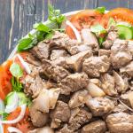 Bò Lúc Lắc sur une assiette de cresson et de tranches de tomate et concombre