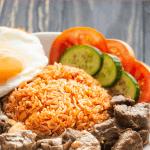 Bò Lúc Lắc sur une assiette avec surce de tomate, tranches de concombre et de tomate et un œuf au plat