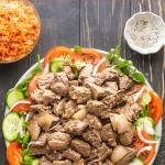 Bò Lúc Lắc sur une assiette de tranches de cresson, de concombre et de tomate à côté d'un bol de riz aux tomates et d'un plat de sel et poivre