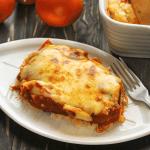 Une tranche de riz aux côtes de porc cuit au four sur une assiette avec une fourchette entourée de tomates et le plat de service
