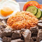 Cơm Đỏ sur une assiette avec Shaking Beef, un œuf au plat et des tranches de concombre et de tomate