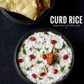 riz caillé servi dans un bol en bois sur un tableau noir gris foncé. le riz caillé est garni de feuilles de coriandre hachées, de quelques arilles de grenade et de frites séchées au soleil. papaddum frit servi en accompagnement.