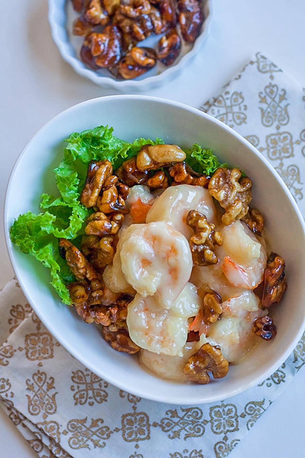 Crevettes au miel et aux noix dans un bol blanc, aux noix confites, prêtes à être servies.