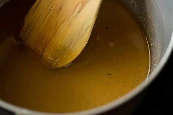 en remuant la solution de sucre avec une spatule en bois