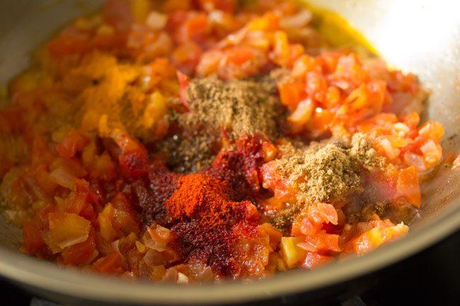 épices moulues ajoutées aux tomates pour faire du curry de pommes de terre