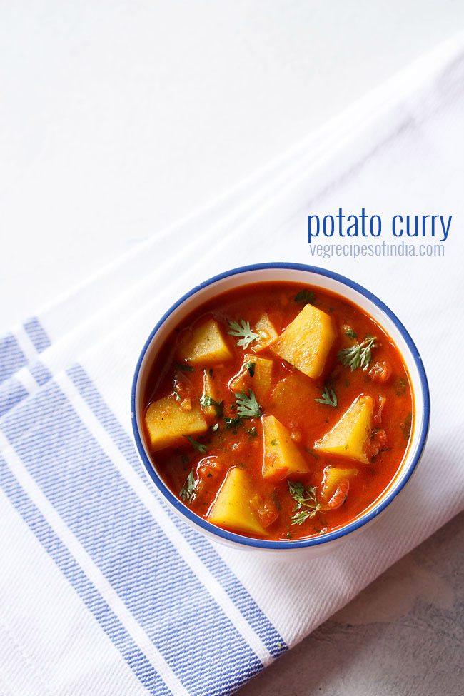 Pommes de terre au curry dans un bol blanc à rebord bleu sur une serviette blanche bordée de bleu