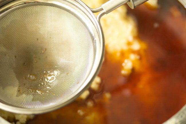 solution de jaggery filtrée avec une passoire dans le riz cuit et les lentilles