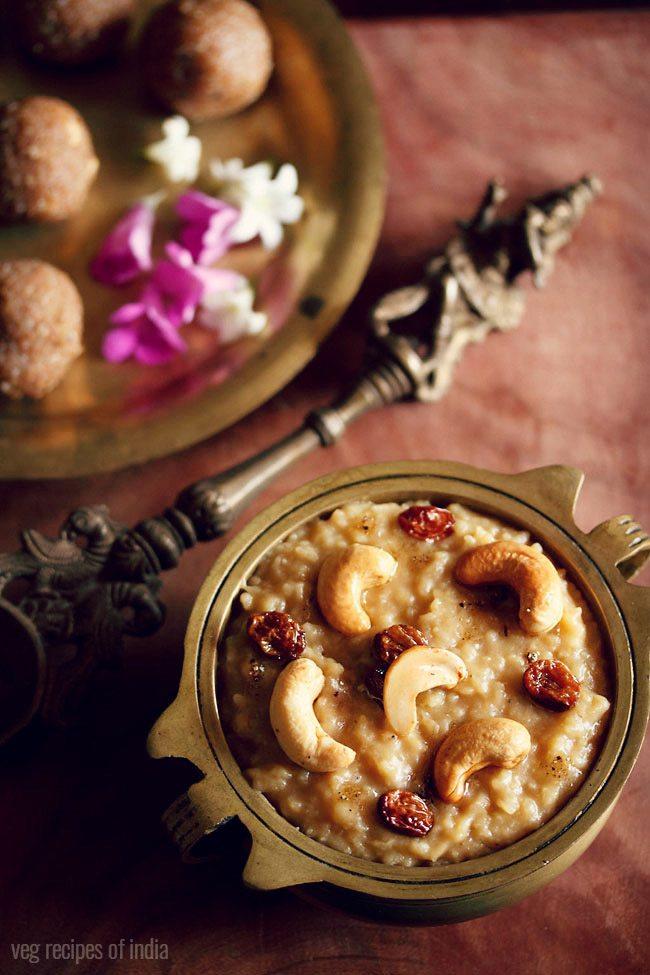 Sakkarai pongal servi dans une casserole en laiton antique avec un côté d'une cuillère en laiton antique et du ladoo et des fleurs rose et blanc foncé sur une plaque en laiton