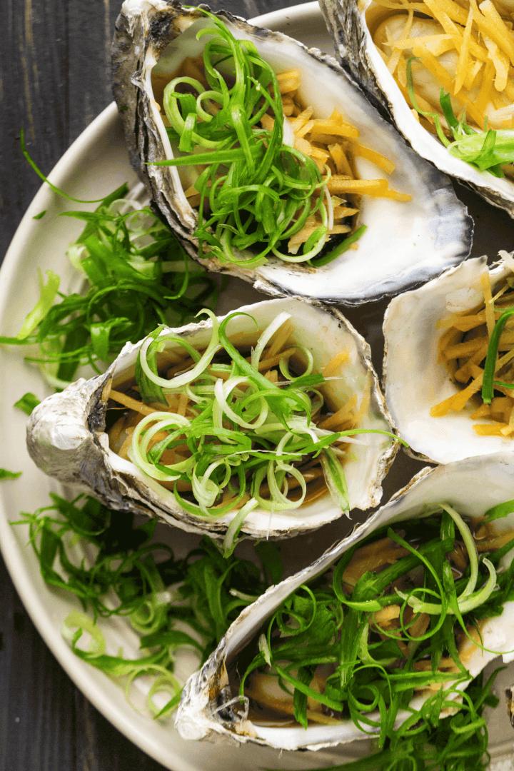Huîtres à la vapeur au gingembre et échalotes sur une assiette