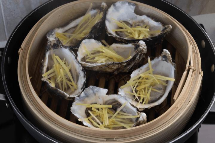 Huîtres avec gingembre coupé en julienne sur eux dans un bateau à vapeur en bambou