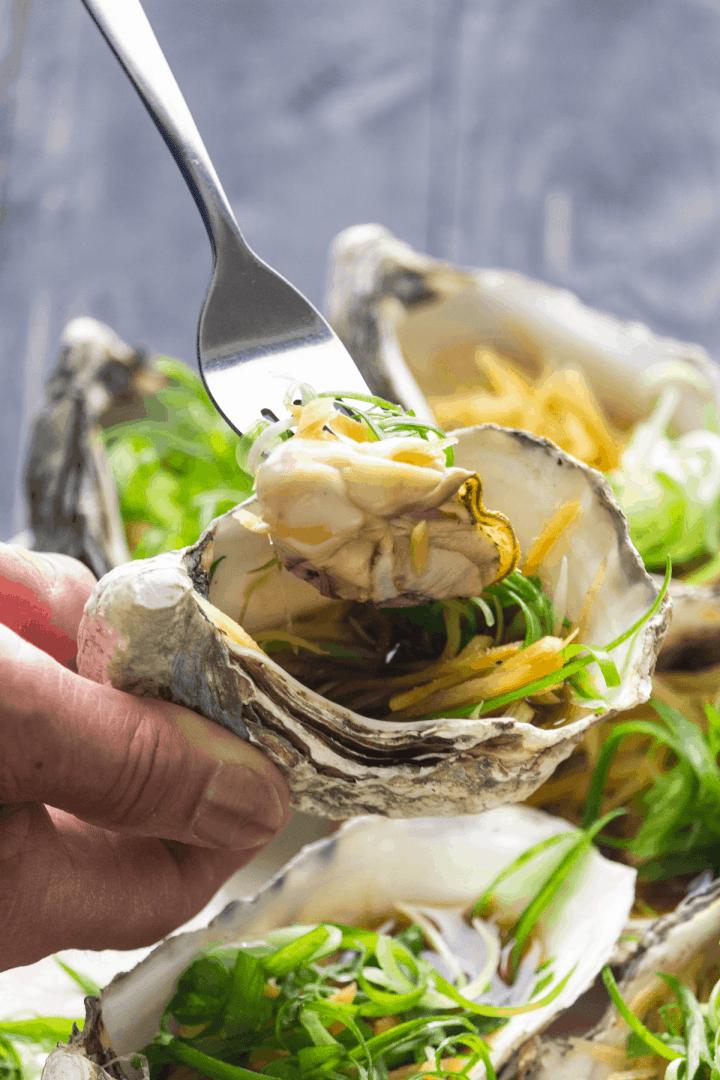 Une main tenant une fourchette tenant une huître au gingembre et échalotes