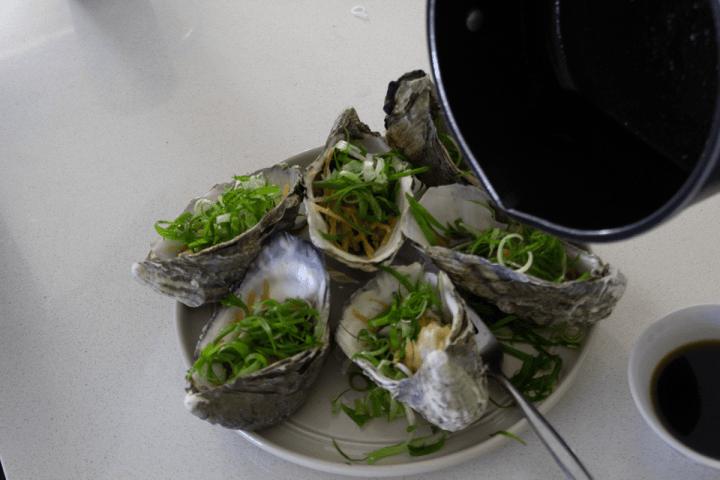 Une casserole verser de l'huile dans les huîtres garnies d'oignons de printemps et de gingembre sur une assiette