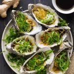 Huîtres vapeur au gingembre et échalotes sur une assiette avec un plat de sauce soja légère
