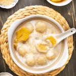 Boules de riz gluant vietnamien dans un bol avec une cuillère à l'intérieur entouré d'un plat de graines de sésame et d'un bol de boulettes de riz gluant.