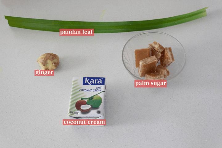 Une feuille de pandan entourée de gingembre, un bol de sucre de palme et un contenant de crème de coco.