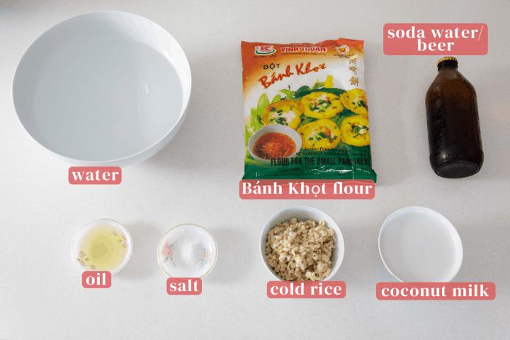 Un bol d'eau avec un sac de farine de banh khot et des plats d'huile, de sel, de riz d'un jour et de lait de coco.