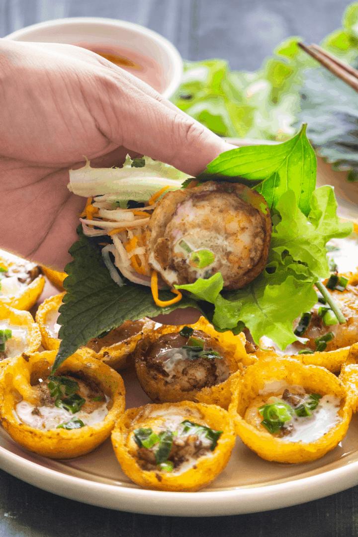 Bánh Khọt sur une assiette avec une main en tenant un enveloppé de salade.
