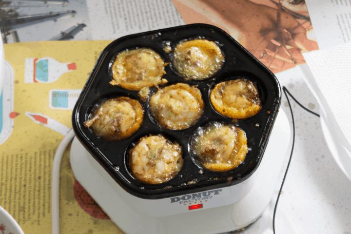 Banh khot cuit dans une machine à beignets.