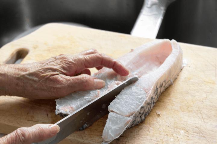 Mains tenant un steak de poisson tandis qu'un couteau coupe au centre.