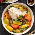 Soupe aigre vietnamienne dans un bol près d'une assiette d'herbes fraîches et plat de sauce.
