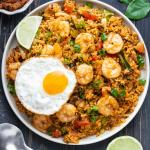 Tom Yum Fried Rice sur une assiette avec un œuf au plat dessus et un quartier de citron.