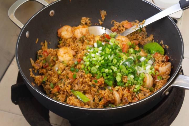 Oignons de printemps hachés sur riz frit Tom Yum dans un wok avec une spatule en métal.
