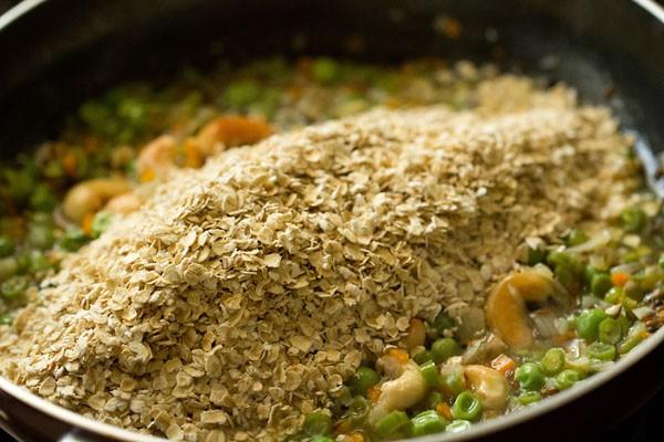 flocons d'avoine rôtis ajoutés sur le mélange de légumes dans une casserole
