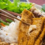 Nouilles et tofu frit étant retenu par des baguettes dans un bol.
