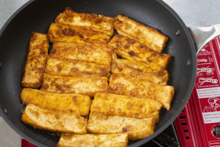 Tofu mariné saisissant dans une poêle.