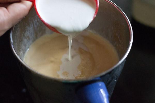la crème étant versée dans le mélangeur avec une tasse à mesurer rouge