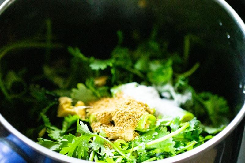 Cumin en poudre et sel versés sur les feuilles hachées dans un mélangeur.