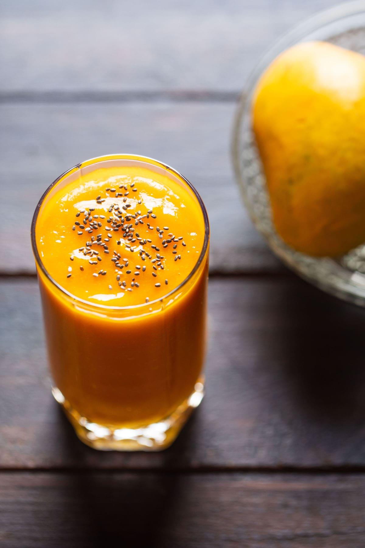 Gros plan de jus de mangue dans un verre garni de graines de chia sur une table en bois avec un côté de mangues sur un bol en verre