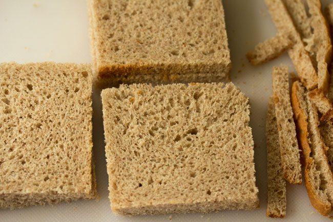 Bords de pain de blé entier parés sur une planche à découper blanche