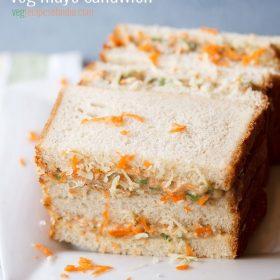 Sandwich à la mayonnaise garni de carottes râpées et de fromage sur une assiette carrée blanche