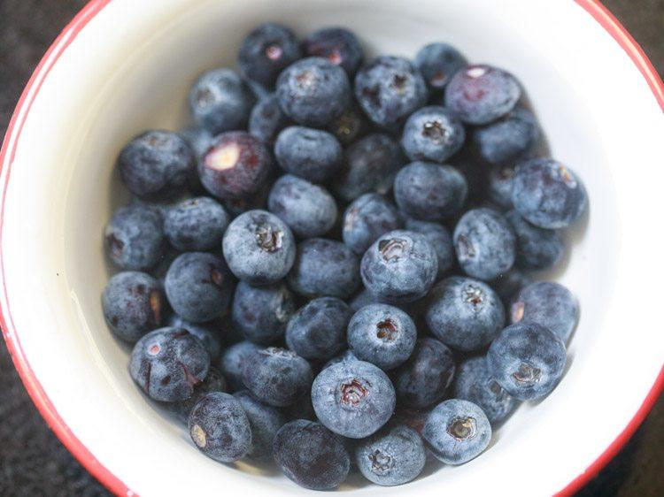 myrtilles dans un bol blanc à rebord rouge pour faire une recette de smoothie aux bleuets