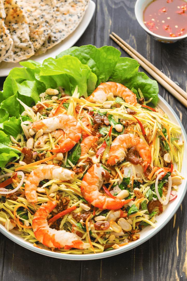 Salade de mangue vietnamienne sur une assiette à côté de baguettes.